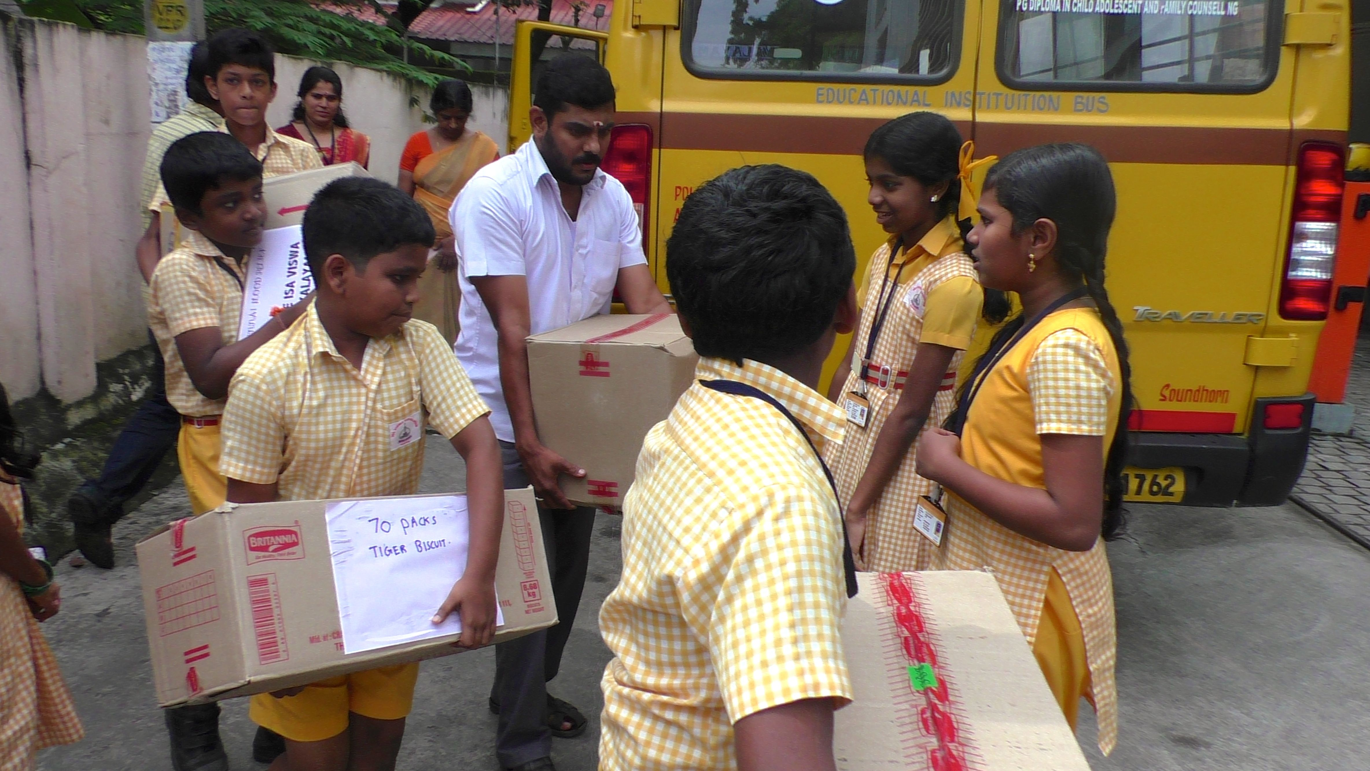 Students of Isa Viswa Vidyalayam unload materials for Chennai relief