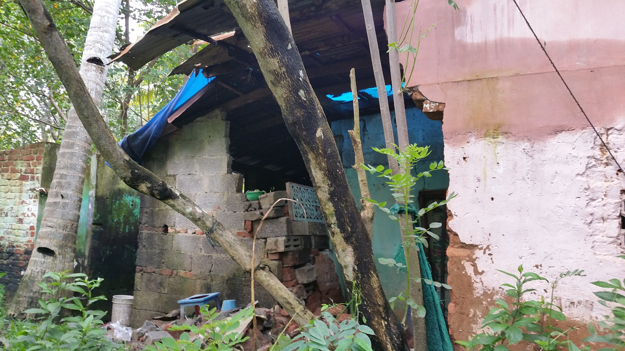 House with fallen wall in a Trivandrum slum after floods